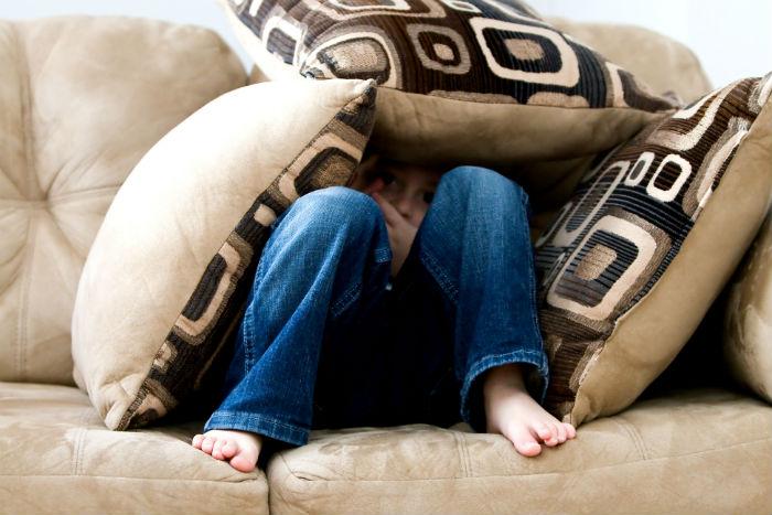enfant caché dans un fort de coussins de canapé